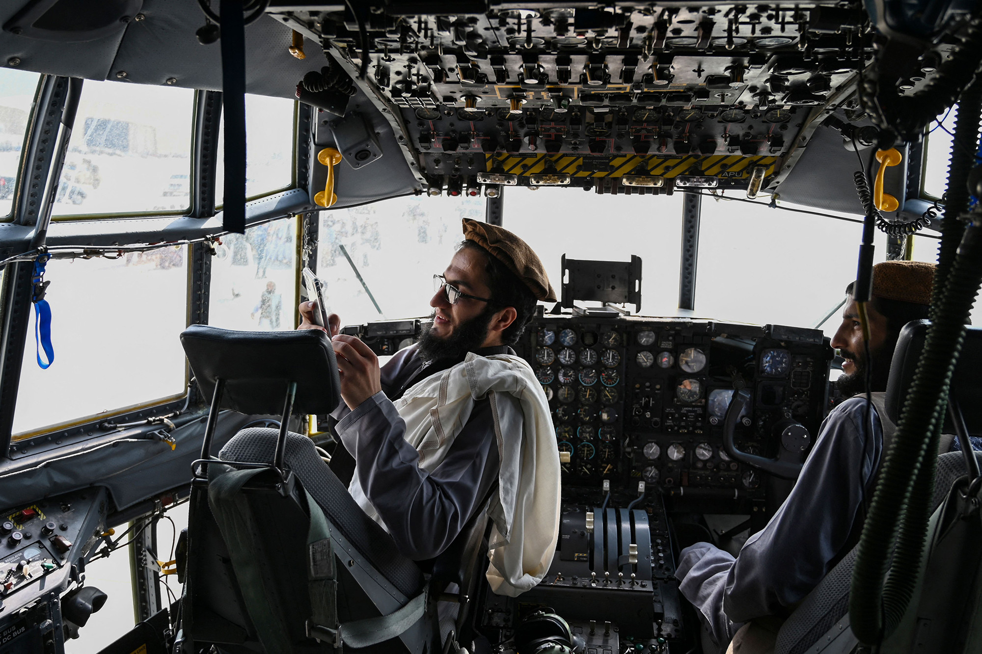Taliban fighters sit in the cockpit of an Afghan Air Force aircraft.